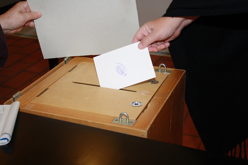 A person putting a ballot paper into a ballot box.