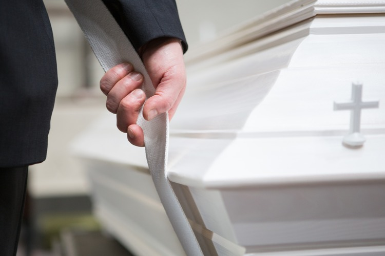 A close-up of a person carrying a coffin.
