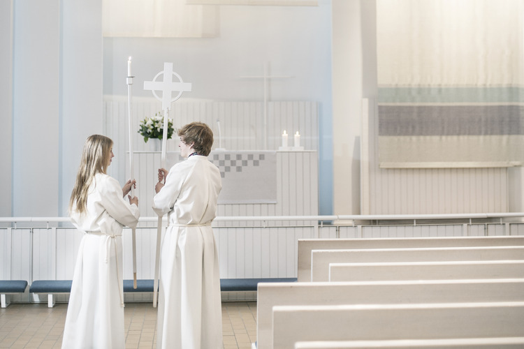 Two teens wearing white albs in confirmation ceremony at church.