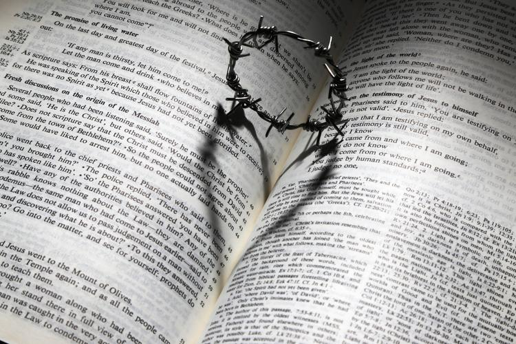 An open Bible with a small crown of thorns on top. The crown casts a shadow shaped like a heart on the Bible.