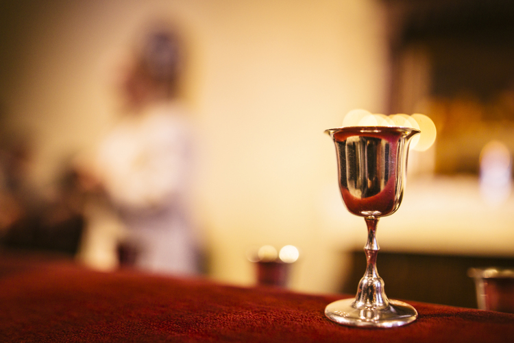 A chalice on the altar. In the background, a priest is sharing the Eucharist.