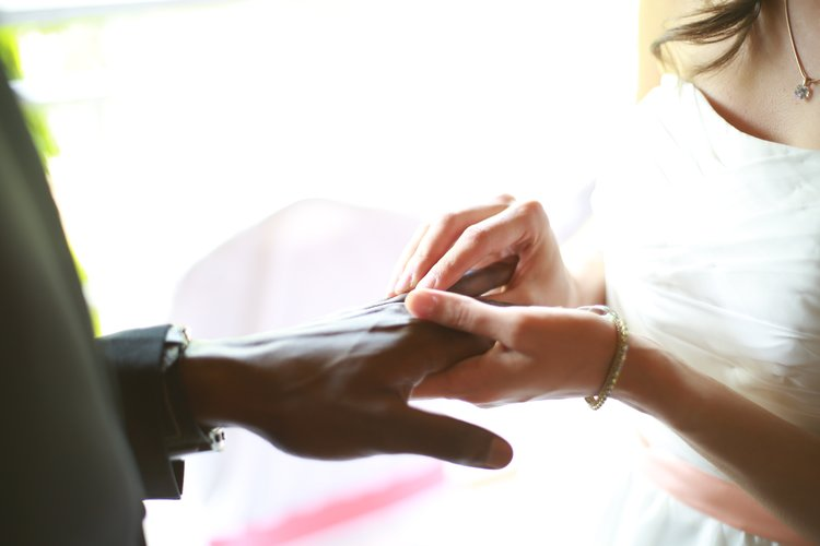 A bride and groom putting on their wedding rings.