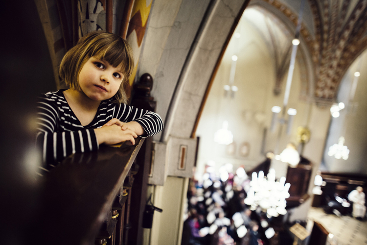 A child looking at the camera and leaning on the parapet of the balcony inside the Church of St. Lawrence